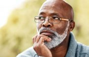 An older gentleman is thinking