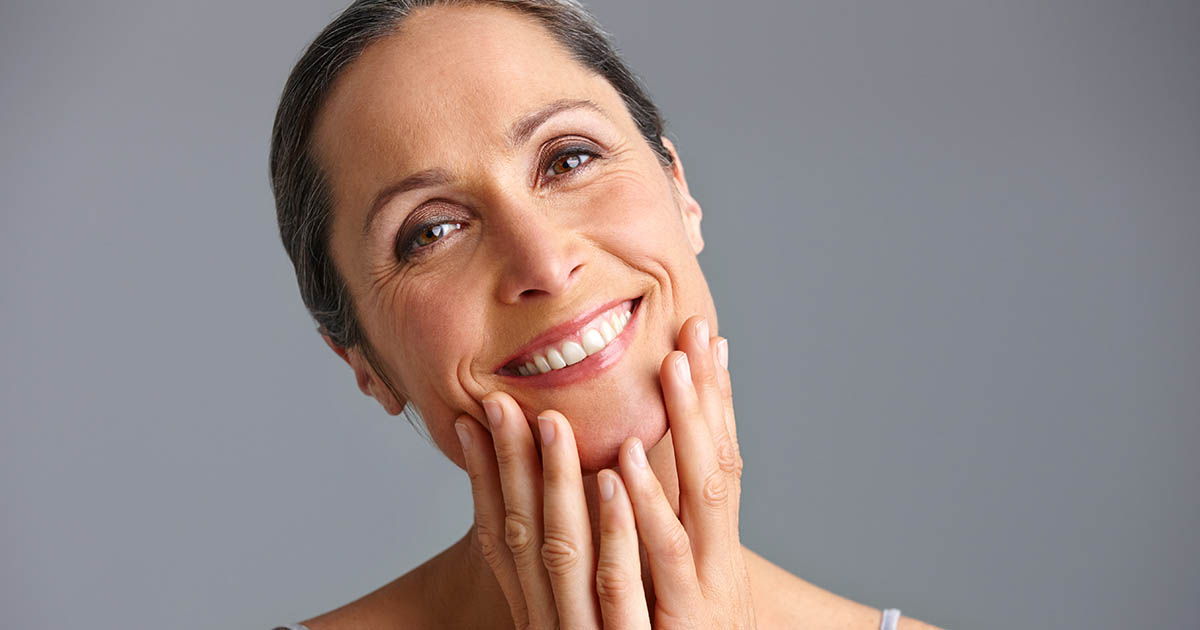 Mature woman smiling and touching her face