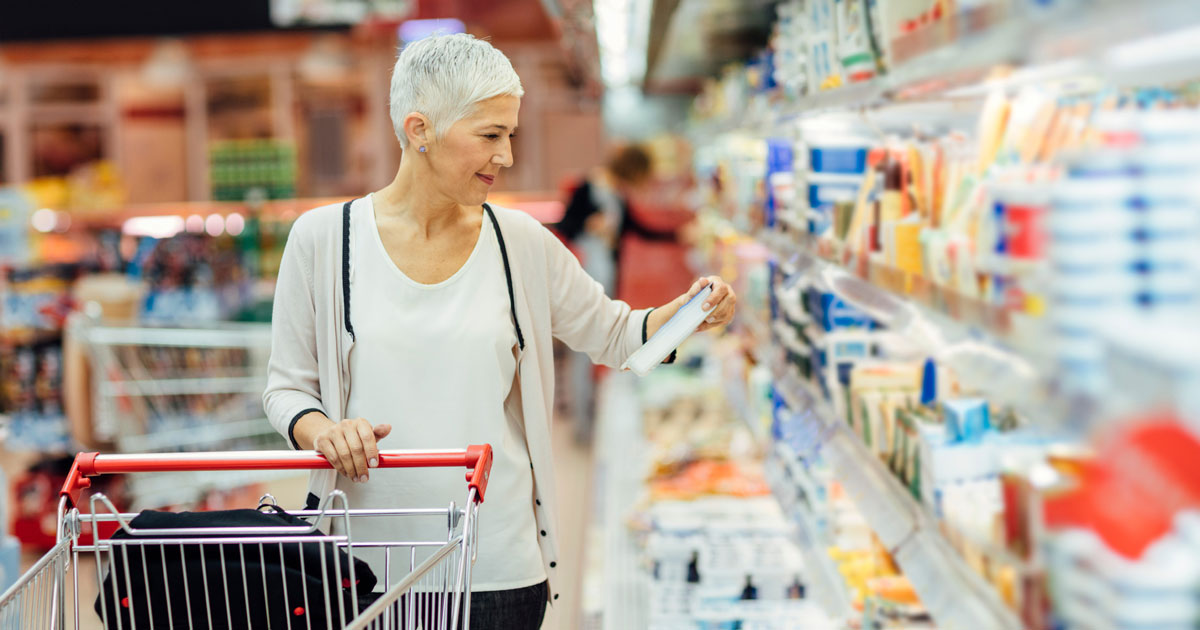 A woman is grocery shopping and reading food labels