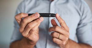 Mature man is using a lancet on his finger tip