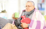A man is holding a hot water bottle in his hands