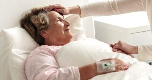 An older woman is laying in a hospital bed