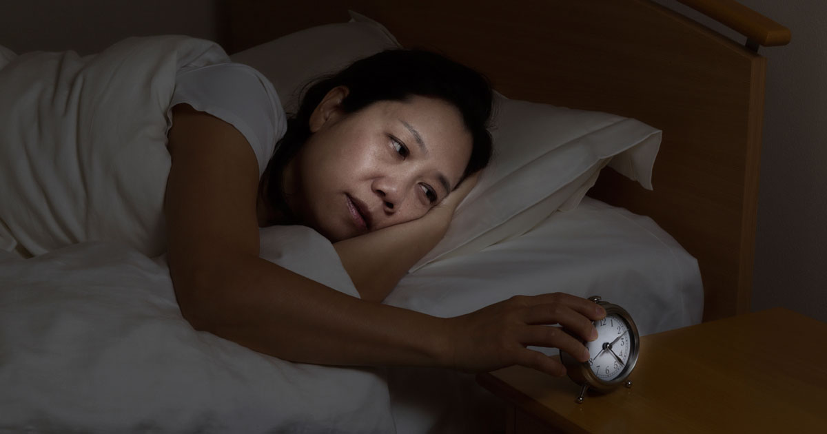 Woman checking her alarm clock in the middle of the night