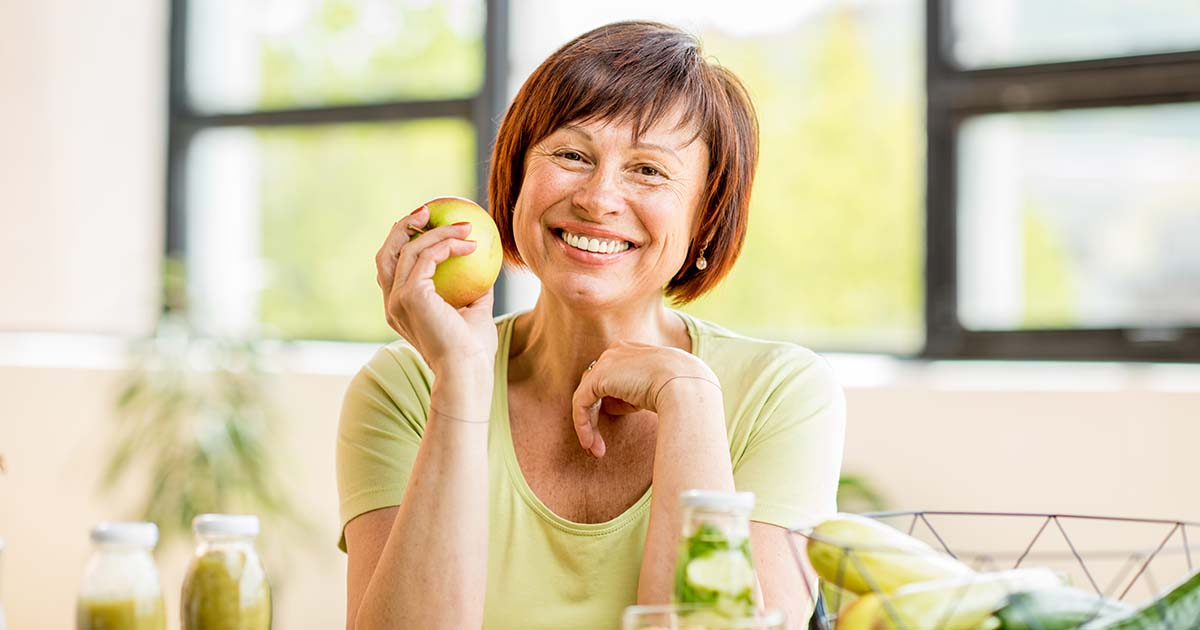 Woman is smiling with apple in hand