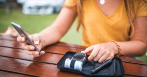 a young woman monitoring her blood sugar levels at a park bench, a part of type 1 diabetes treatment