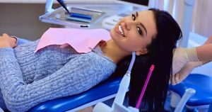 a young woman lying on a chair at at a dental appointment