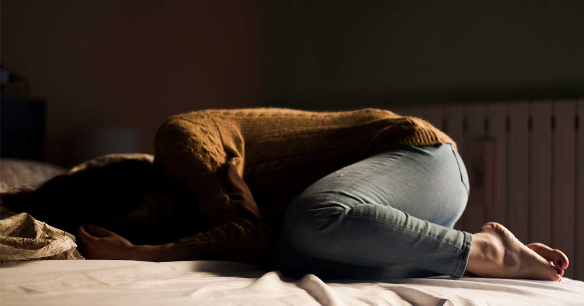 a woman with depression curled up on a bed in a dark room