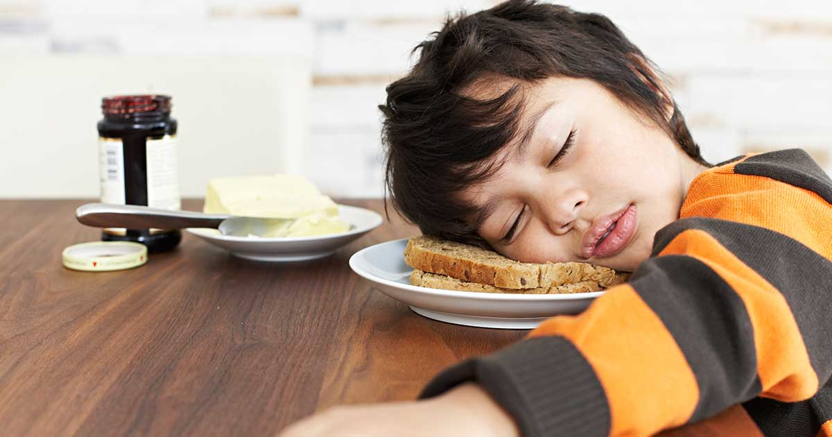 A young boy sleeping on a plate of toast.