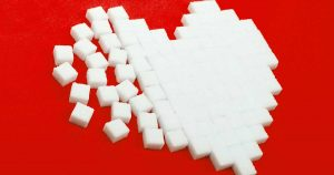 A heart of sugar cubes against a red background.